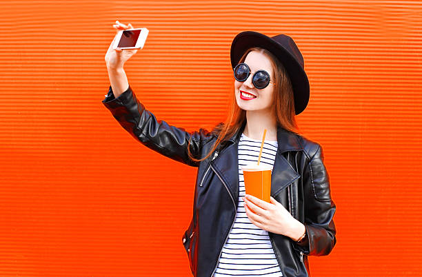 fashion smiling young woman taking picture self portrait on smartphone - pics for cool girl stock pictures, royalty-free photos & images