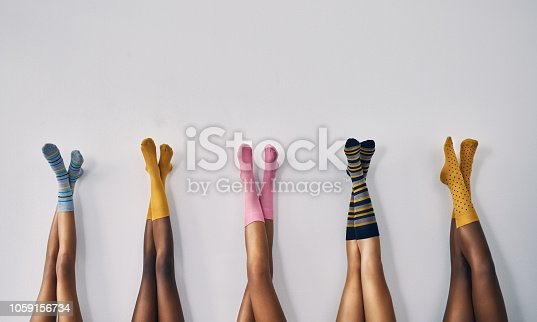 Cropped studio shot of a group of women's legs in a row wearing socks