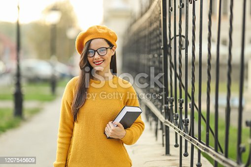 521911045 istock photo Fashion student holding a book 1207545609