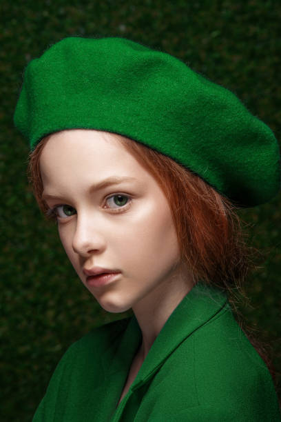 f8507c4a5f8 Fashion studio portrait of cute little redhead girl wearing green clothes.  stock photo