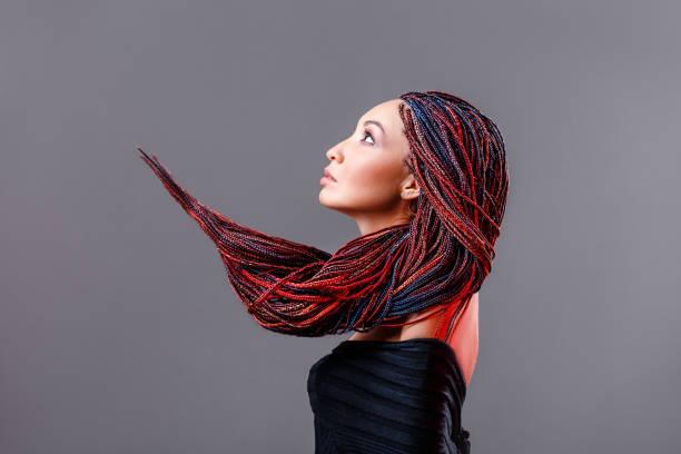 mode-studio-shooting einer gemischten rennfrau mit einer kreativen bunten frisur in form eines zöpfens aus dreadlocks in der technik von zizi geflochten. das konzept der friseurkunst - rote dreads stock-fotos und bilder