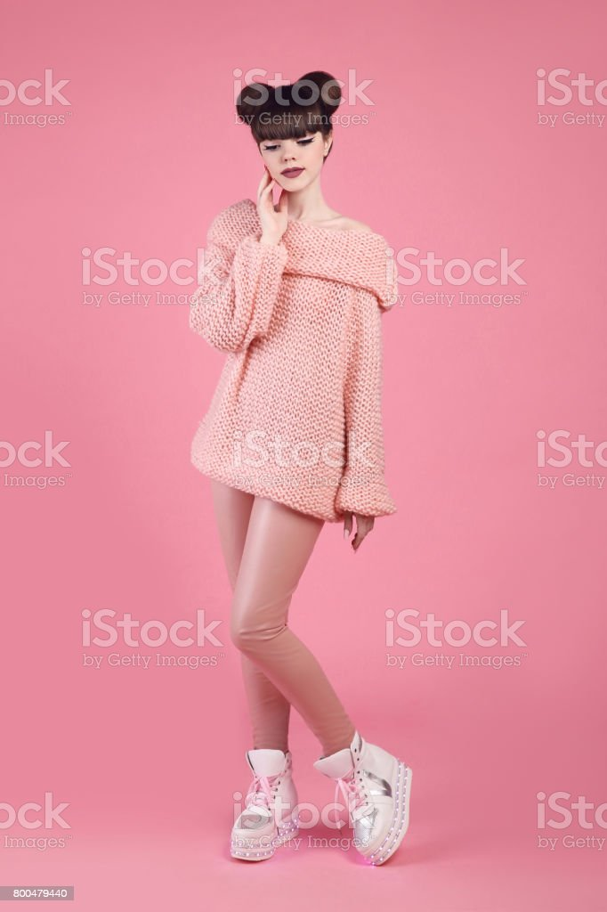 Fashion studio teen look style in boot shoes. Fashionable young girl wears wool jumper and leather pants posing isolated on pink background. stock photo