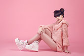 Fashion studio teen look style in shoes. Fashionable young girl wears in wool sweater and leather pants sitting on the floor isolated on pink background.