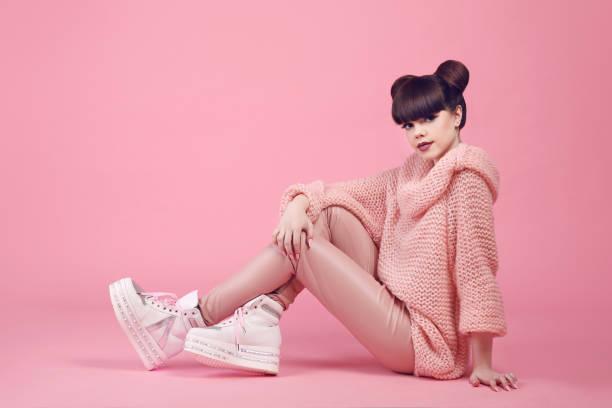 mode studio tiener kijk stijl in schoenen. modieuze jong meisje draagt in wollen trui en lederen broek zittend op de vloer geïsoleerd op roze achtergrond. - street style stockfoto's en -beelden
