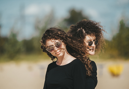 Fashion style portrait of young pretty stylish girls with long curly hair wearing black sunglasses