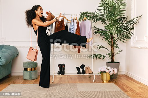 Fashion stylist laughing in studio at clothes rack