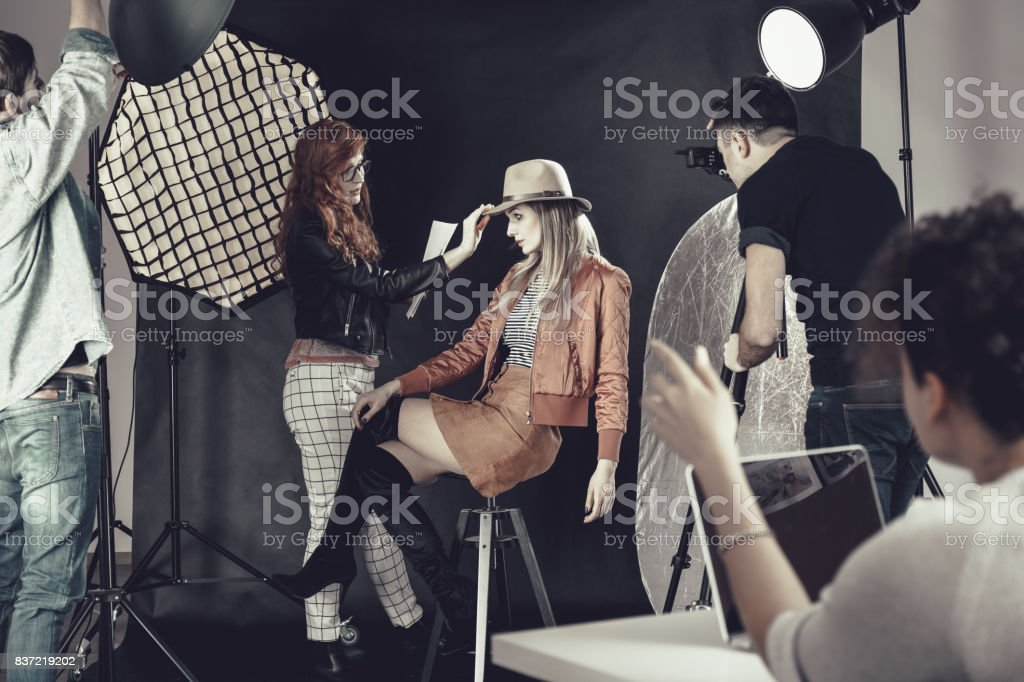 Fashion stylist with model at photoshoot stock photo