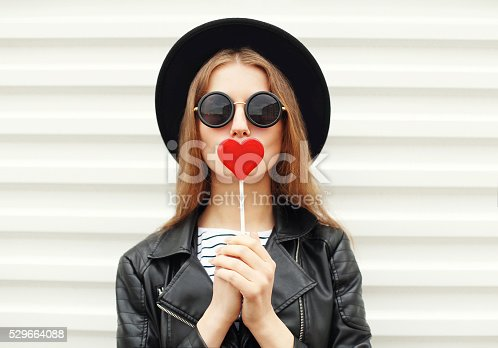 529664088istockphoto Fashion sweet woman having fun with lollipop over white background 529664088