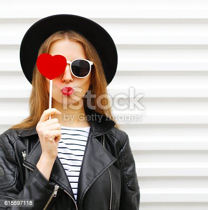 529664088istockphoto Fashion sweet woman with red lips air kiss lollipop heart 615597118