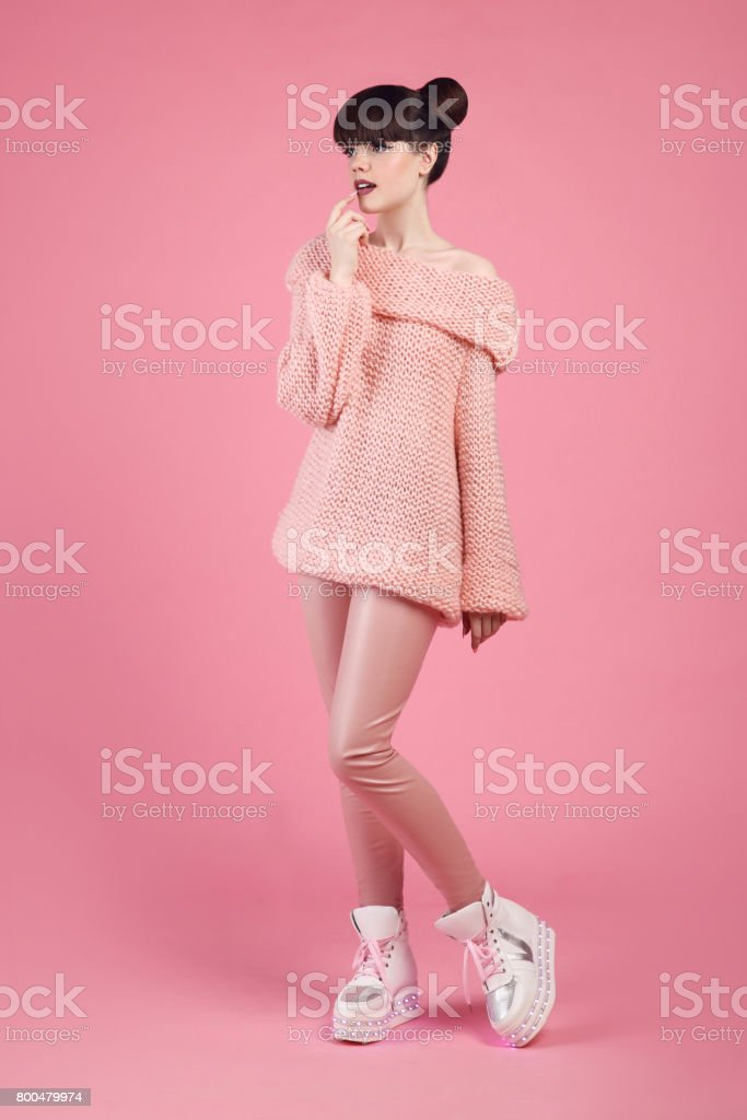 Fashion teen look style in boot shoes. Fashionable young girl dressed wool jumper and leather pants posing isolated on studio pink background. stock photo