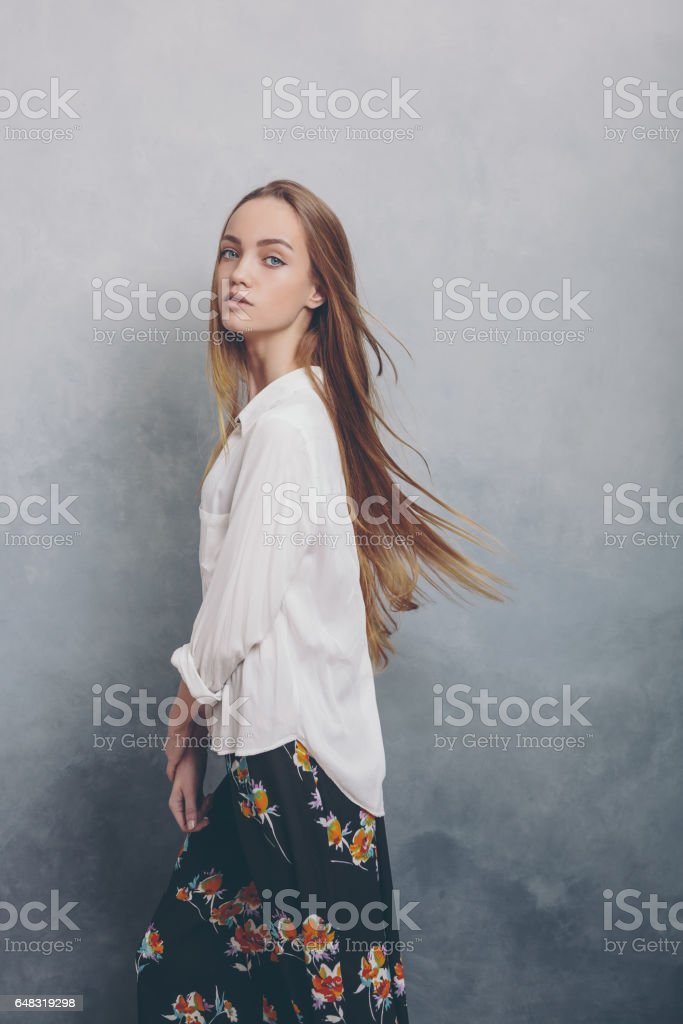 Fashion teenager girl standing against blue textured grunge wall background stock photo