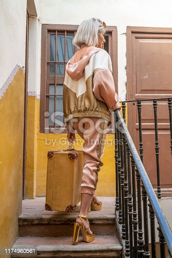 Fashion tourist woman climbing vintage stairs with baggage and golden high heels in Mediterranean city