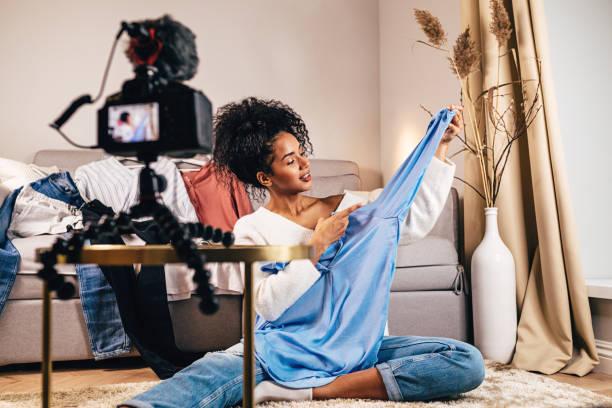 時尚投票人在客廳裡對休閒襯衫的恢復視頻 - influencer 個照片及圖片檔