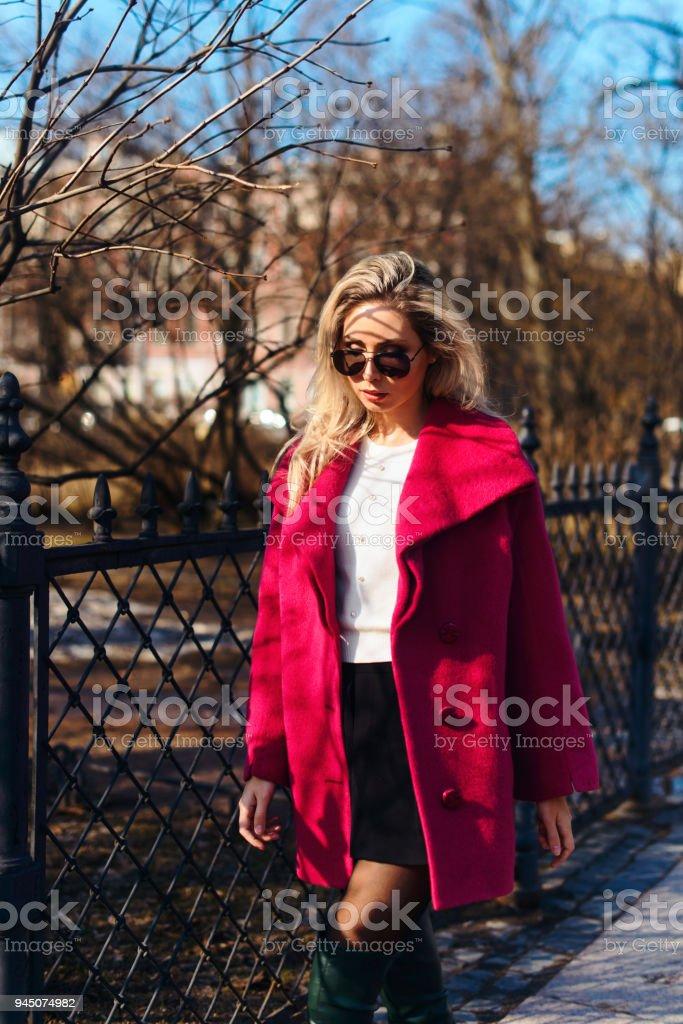 b05b6fbf6491b Fashion style jeune beau élégante femme marchant en manteau rose, lunettes  de soleil, shorts