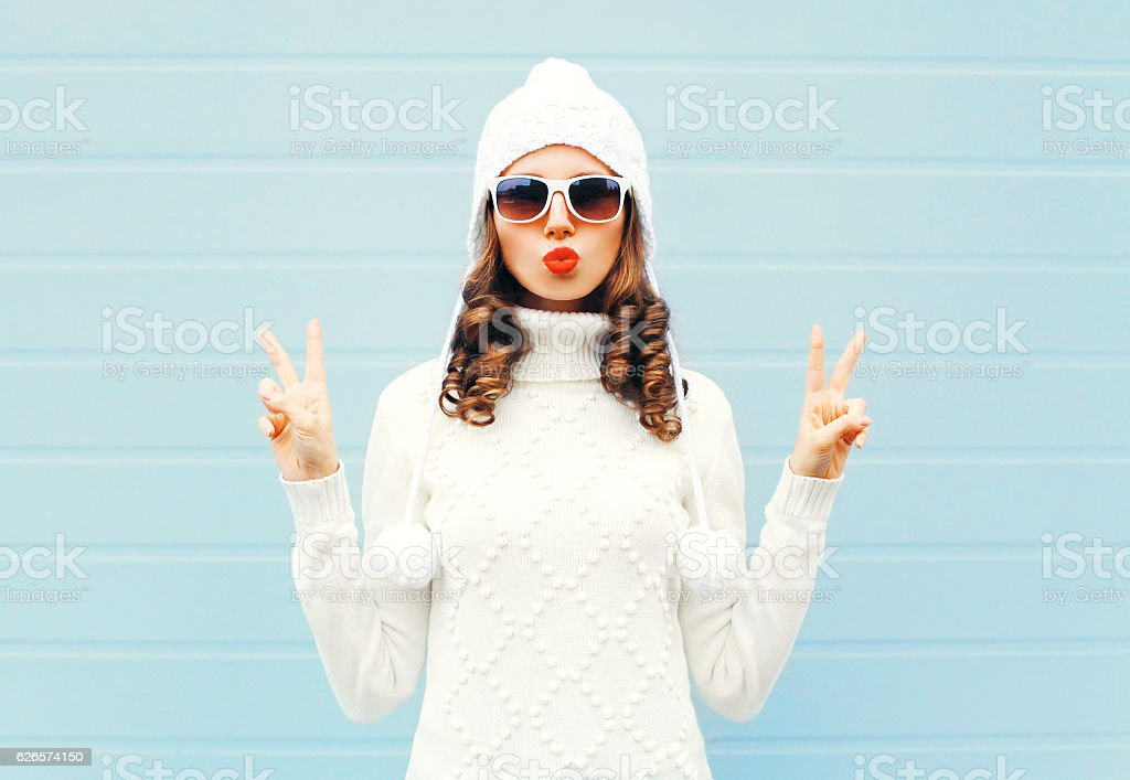 Fashion woman blowing red lips makes air kiss stock photo