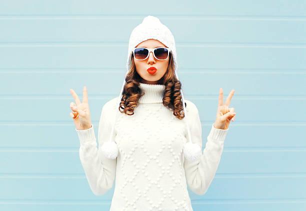 fashion woman blowing red lips makes air kiss - moda de invierno fotografías e imágenes de stock