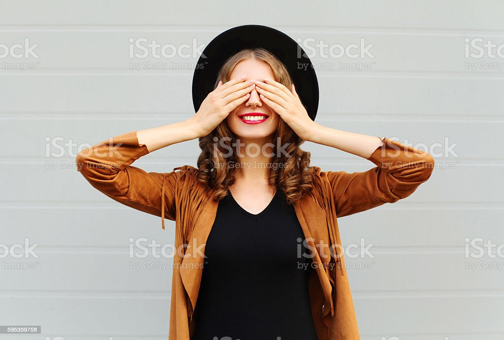 Fashion woman closes eyes smiling wearing hat jacket having fun stock photo