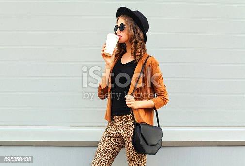 istock Fashion woman drinks coffee cup wearing elegant hat jacket handbag 595358438