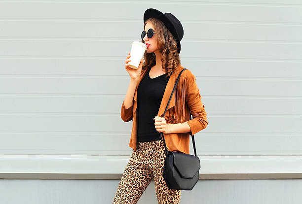 fashion woman drinks coffee cup wearing elegant hat jacket handbag - bedruckte leggings stock-fotos und bilder