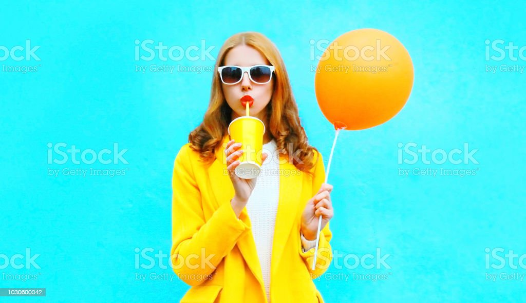 Fashion woman drinks fruit juice holds an orange air balloon on colorful blue background stock photo