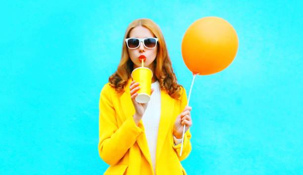 Mode Frau Getränke Fruchtsaft hält einen orangefarbenen Luftballon auf bunten blauen Hintergrund – Foto