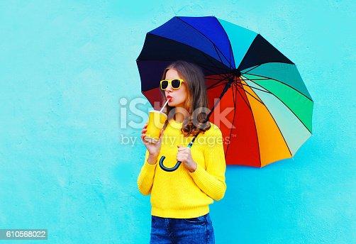 istock Fashion woman fresh fruit juice cup colorful umbrella in autumn 610568022