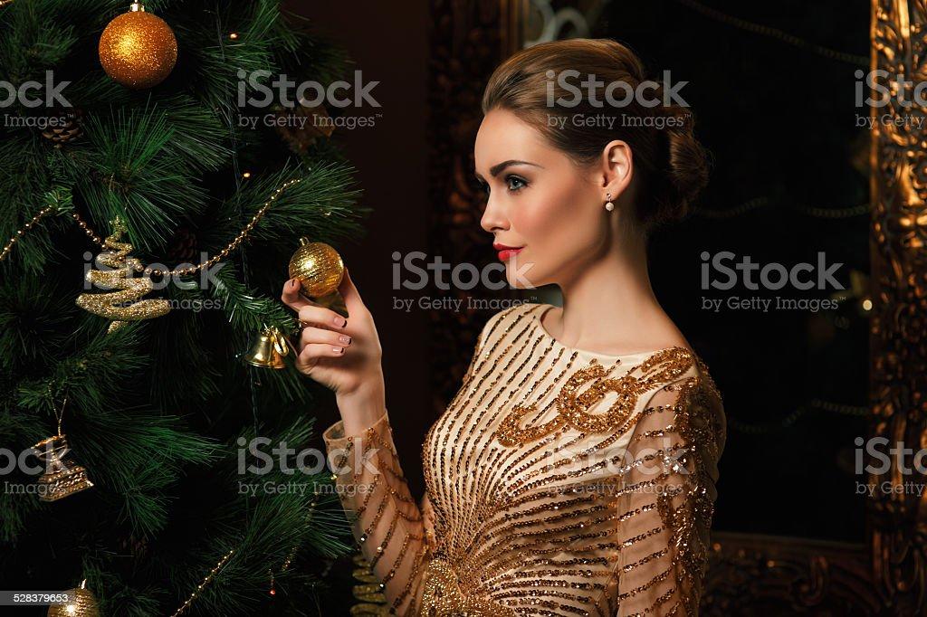 Moda mulher hanged um brinquedo sobre a árvore de Natal - foto de acervo