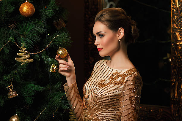 fashion woman hanged a toy on the Christmas tree stock photo