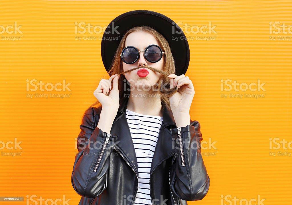 Fashion woman having fun shows moustache hair over orange background stock photo