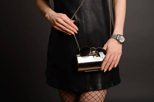Fashion woman hold silver clutch in hand bag and watch near background. Fashion woman hold silver clutch in hand bag and watch near background. Close up stylish accessory luxury watch stock pictures, royalty-free photos & images