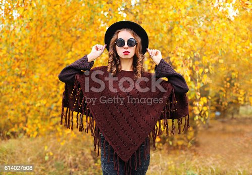 469211680 istock photo Fashion woman in autumn day wearing a black hat poncho 614027508