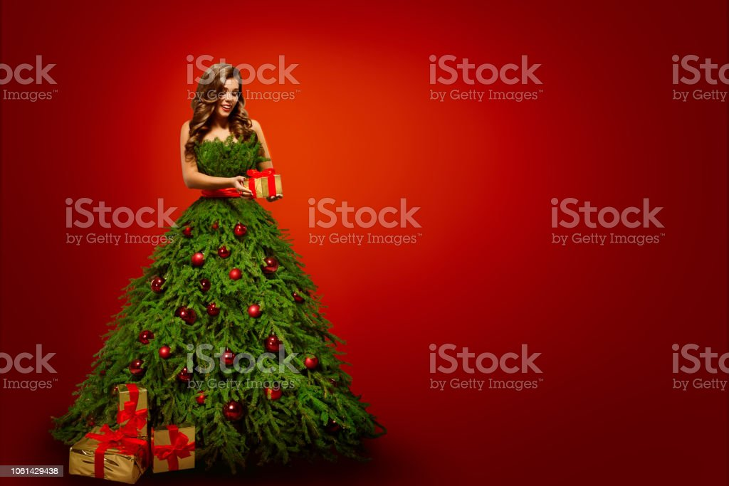 Fashion Woman in Christmas Tree Dress, Model hold Xmas Present Gifts...