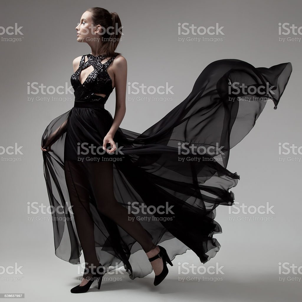 Fashion woman in fluttering black dress. Gray background. stock photo