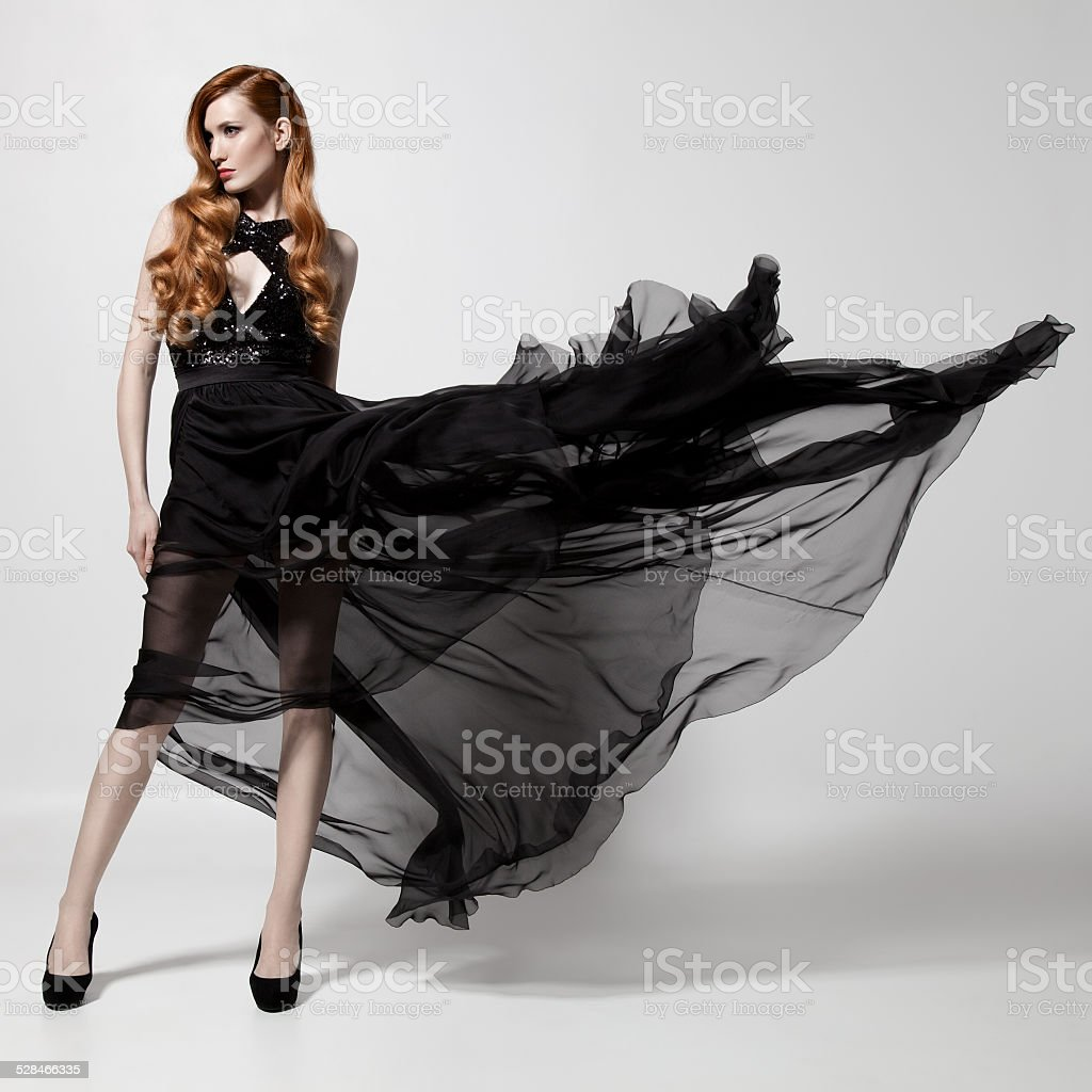 Fashion woman in fluttering black dress. White background. stock photo