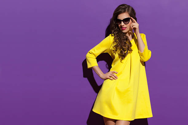 fashion woman in yellow mini dress and sunglasses looking away - mini dress stock photos and pictures