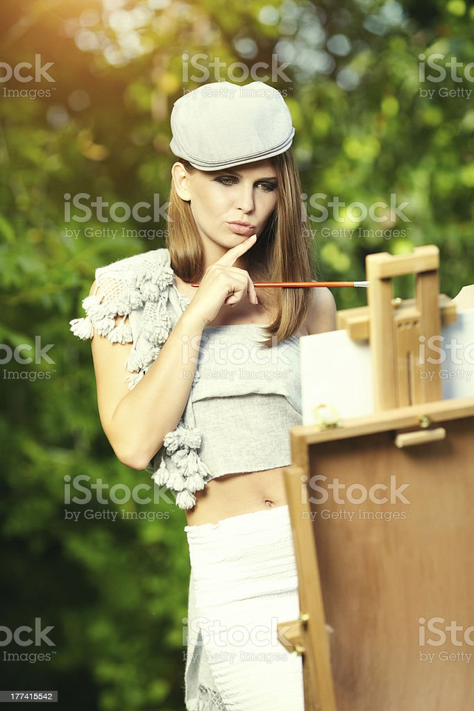 Fashion woman is painting. Open air session. royalty-free stock photo