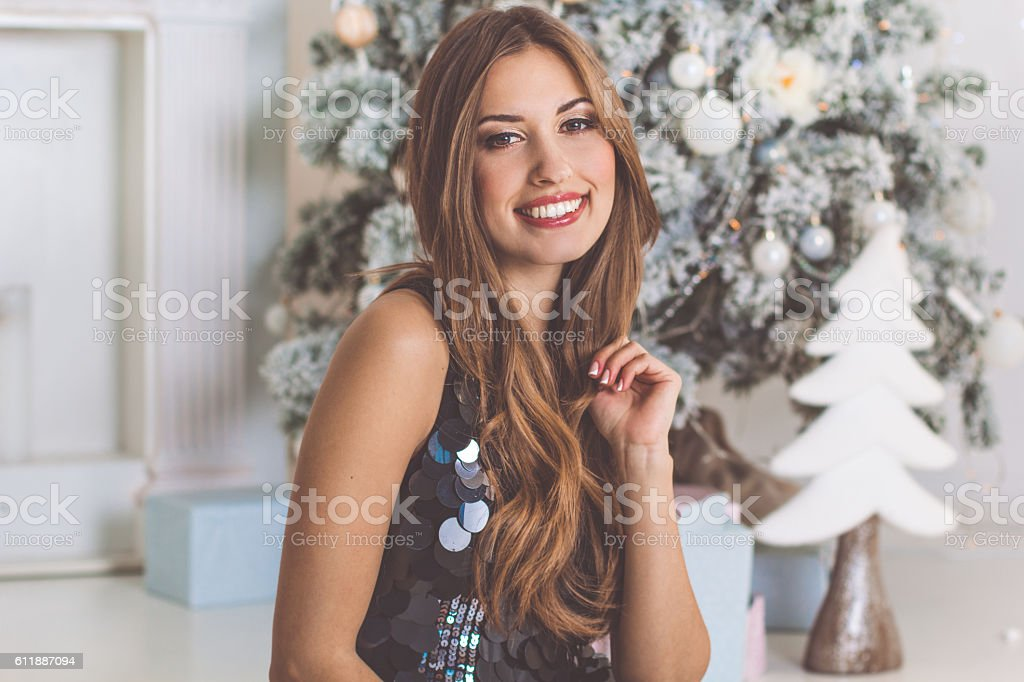 Fashion woman is sitting near christmas tree - Royalty-free Adult Stock Photo