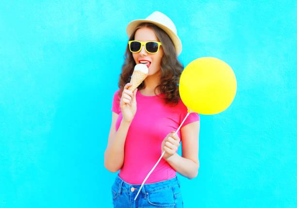mode-frau versucht eis trägt einen strohhut und rosa t-shirt über bunten blauen hintergrund - eis ballons stock-fotos und bilder