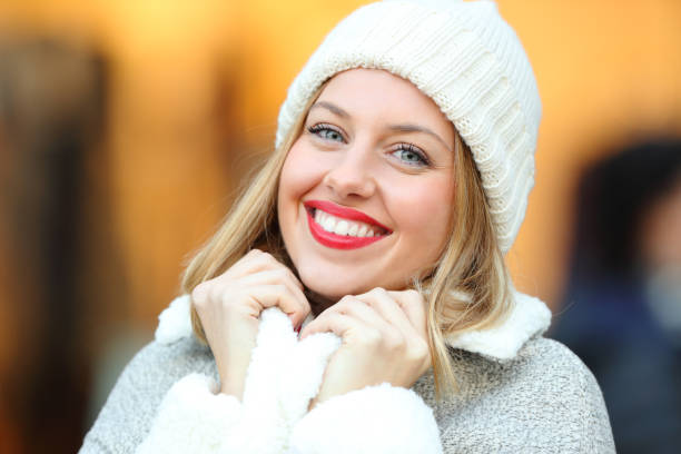 Fashion woman keeping warm on the street in winter Portrait of a happy fashion woman looking at camera keeping warm on the street in winter bonnet stock pictures, royalty-free photos & images