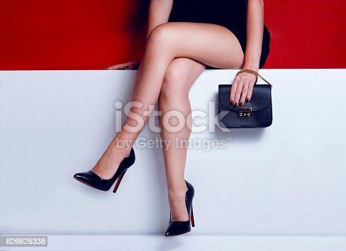 istock Fashion woman legs dress black purse and high heels shoes 626626338