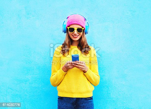 istock Fashion woman listening music in headphones browsing smartphone colorful 614030776