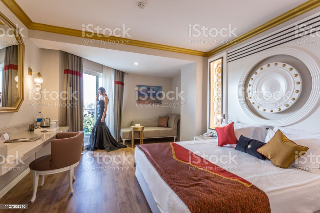 Fashion Woman looking from window in hotel room