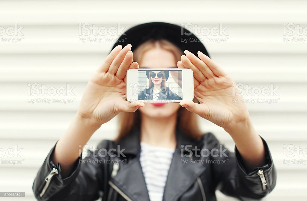 Fashion woman makes self portrait on smartphone view of screen stock photo