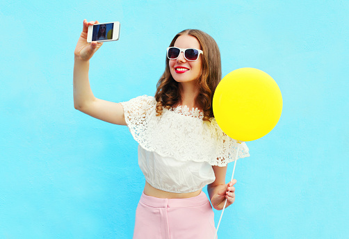 istock Fashion woman makes self portrait on smartphone with air balloon 543469422