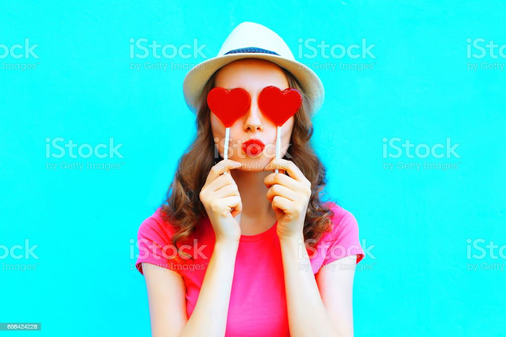 Fashion woman making a kiss hiding red lollipop shape of a heart her eyes over colorful blue background stock photo