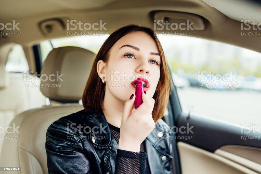 Moda mulher inventar seus lábios com batom vermelho no carro - foto de acervo