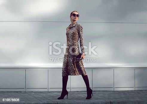 istock Fashion woman model in leopard dress walking in evening city 616878608