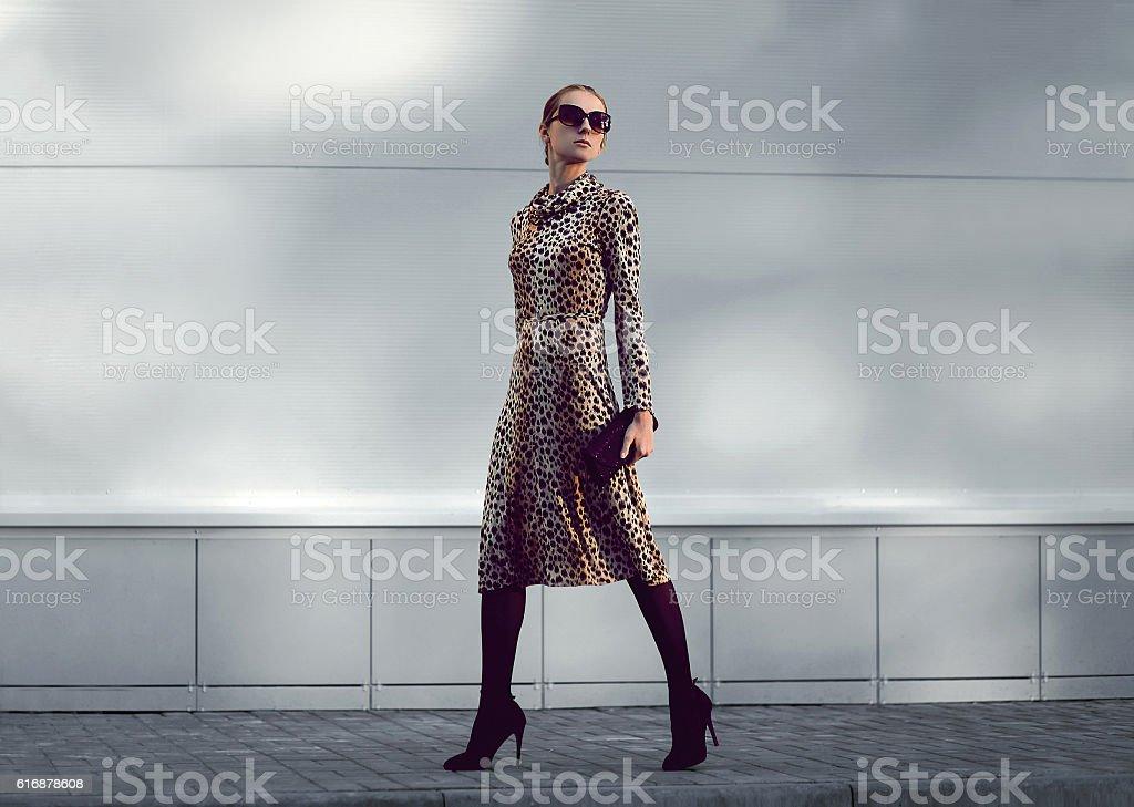 Fashion woman model in leopard dress walking in evening city stock photo