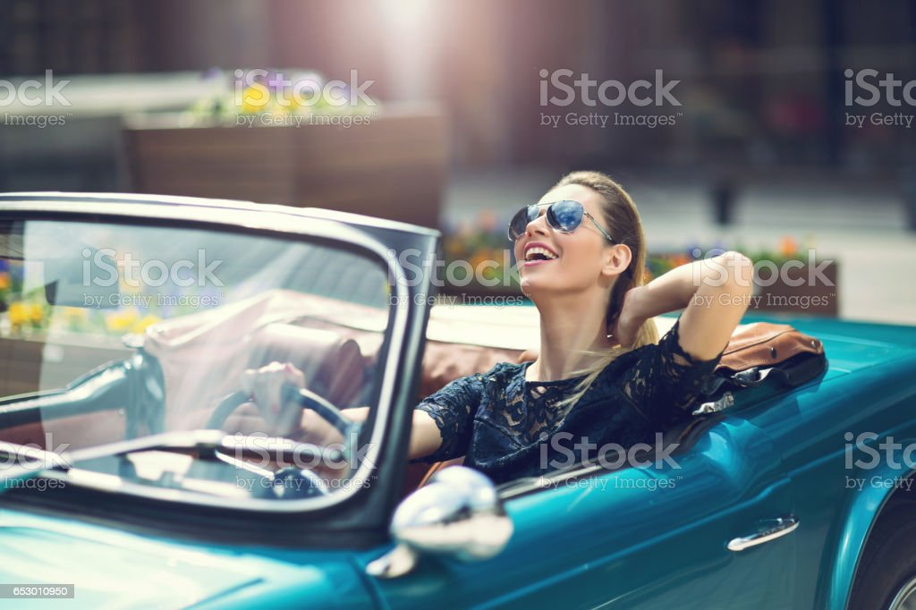 Fashion woman model in sunglasses sitting in luxury retro car stock photo