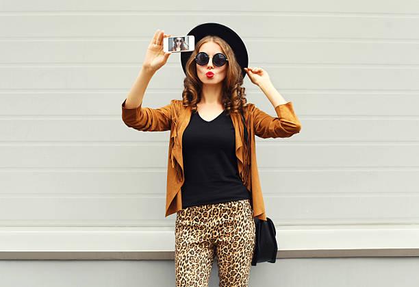 Fashion woman model taking photo picture self-portrait on smartphone stock photo